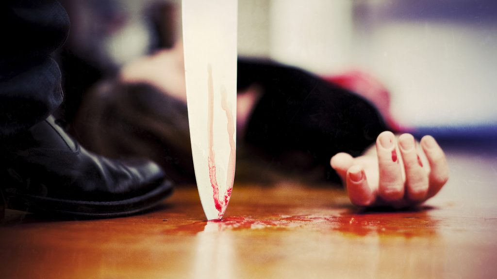 Close up on a bloody knife planted on a wooden floor, a killing scene