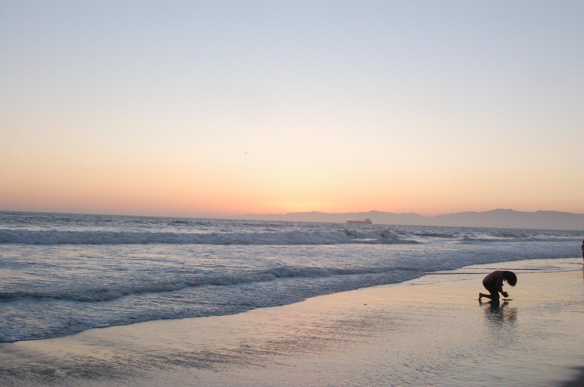 Figure kneeling on beach